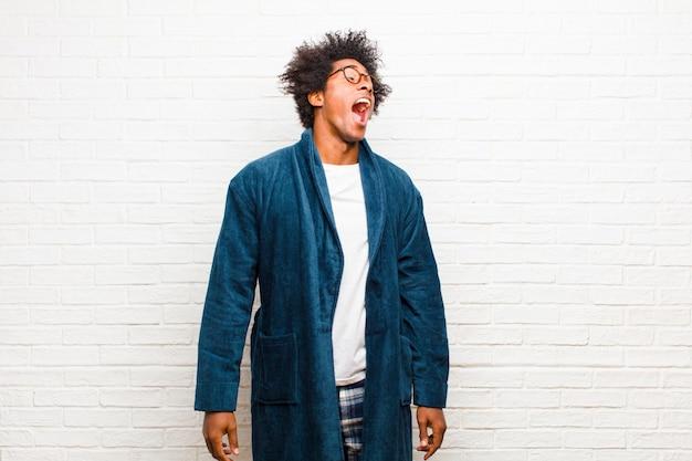 Giovane uomo di colore che indossa un pigiama con abito urlando furiosamente, gridando in modo aggressivo, guardando il muro di mattoni stressato e arrabbiato
