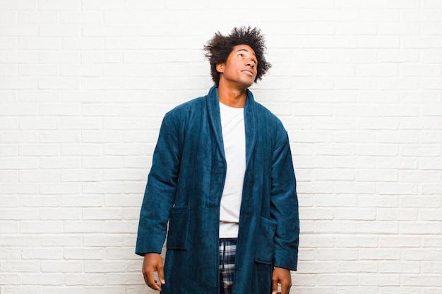 Giovane uomo di colore che indossa un pigiama con abito con un'espressione preoccupata, confusa, all'oscuro, alzando lo sguardo per copiare lo spazio, dubitando contro il muro di mattoni