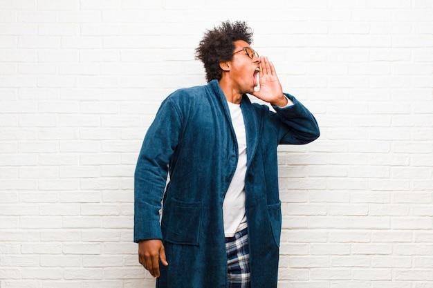 Giovane uomo di colore che indossa un pigiama con abito che urla ad alta voce e rabbiosamente per copiare lo spazio sul lato, con la mano accanto alla bocca contro il muro di mattoni