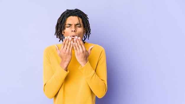 Giovane uomo di colore che indossa l'acconciatura rasta piegando le labbra e tenendo i palmi delle mani per inviare un bacio d'aria.