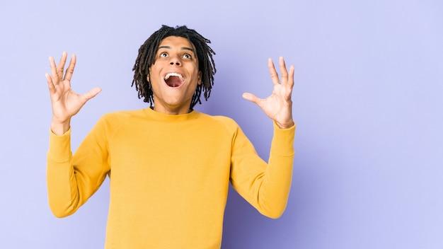 Giovane uomo di colore che indossa l'acconciatura rasta che grida al cielo, alzando lo sguardo, frustrato.
