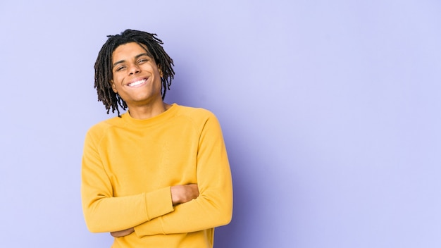 Giovane uomo di colore che indossa l'acconciatura rasta che si sente sicuro, incrociando le braccia con determinazione.