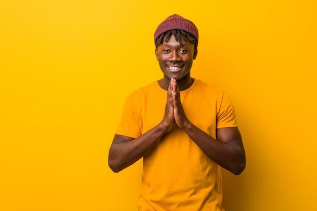 Giovane uomo di colore che indossa rasta su giallo che compongono il piano in mente, creando un'idea.
