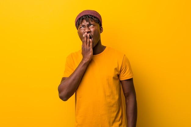 Giovane uomo di colore che indossa rasta su giallo che sbadiglia mostrando un gesto stanco coning bocca con lui mano.