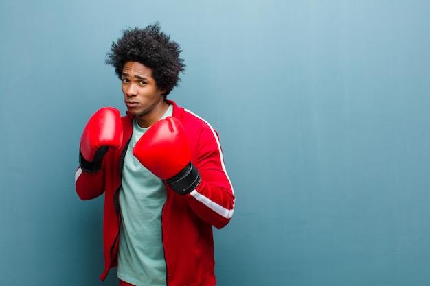 Giovane uomo di colore con i guantoni da pugile contro la parete blu del grunge