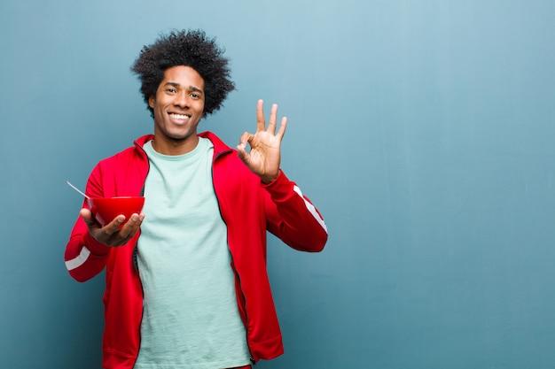Giovane uomo di colore con una ciotola per la colazione contro la parete blu del grunge