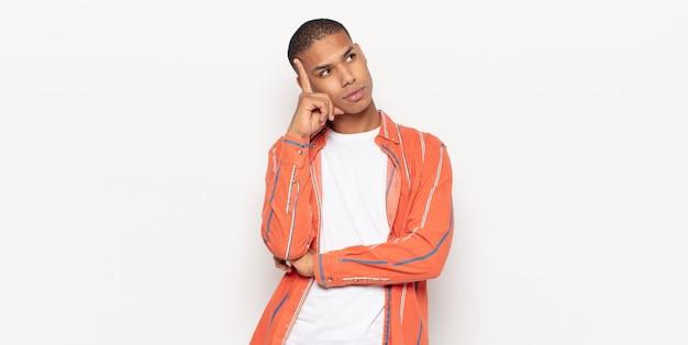 Giovane uomo di colore con uno sguardo concentrato, chiedendosi con un'espressione dubbiosa, guardando in alto e di lato