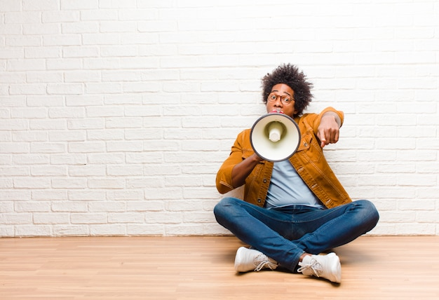 Giovane uomo di colore con un megafono seduto sul pavimento