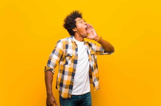 Giovane uomo di colore che urla ad alta voce e rabbiosamente per copiare lo spazio sul lato, con la mano accanto alla bocca contro il muro arancione
