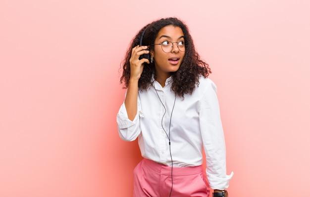 Musica d'ascolto della giovane donna graziosa nera con le cuffie contro la parete rosa