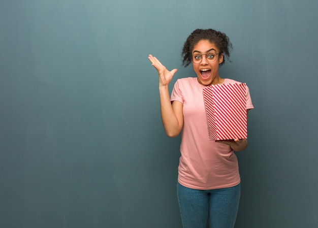 Giovane donna di colore che celebra una vittoria o un successo. ha in mano un secchio di popcorn.