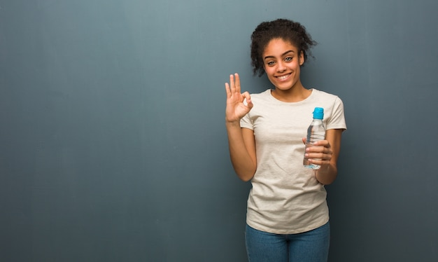 Giovane donna di colore allegra e sicura che fa gesto giusto. ha in mano una bottiglia d'acqua.