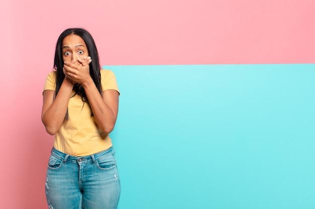 Giovane donna di colore che copre la bocca con le mani con un'espressione scioccata e sorpresa, mantenendo un segreto o dicendo oops. copia il concetto di spazio