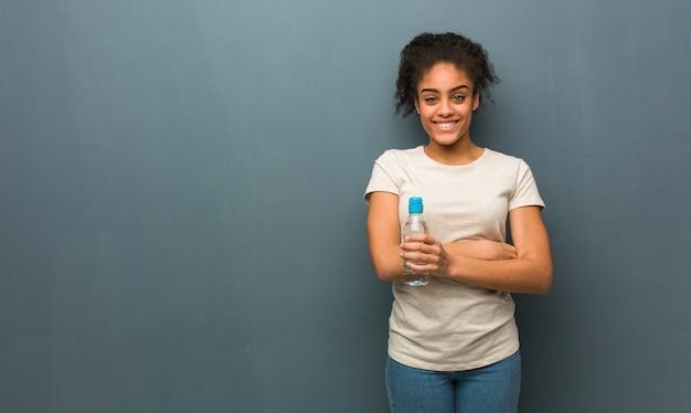 Braccia dell'incrocio della giovane donna di colore, sorridenti e rilassate. tiene in mano una bottiglia d'acqua.