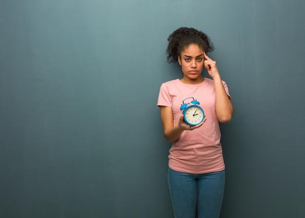 Giovane donna di colore che fa un gesto di concentrazione. ha in mano una sveglia.