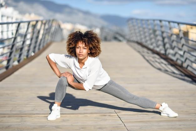 Giovane donna di colore facendo stretching dopo l'esecuzione all'aperto