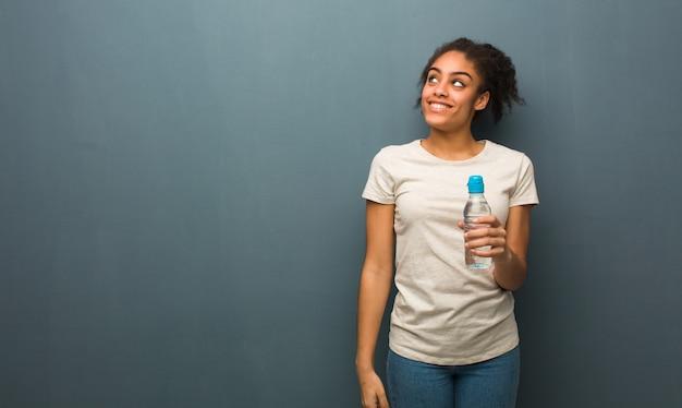 Giovane donna di colore che sogna di raggiungere gli scopi e gli scopi. tiene in mano una bottiglia d'acqua.