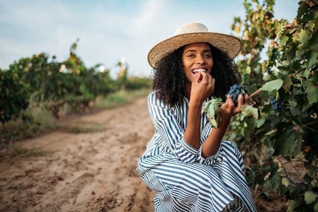 Giovane donna di colore che mangia un'uva in una vigna