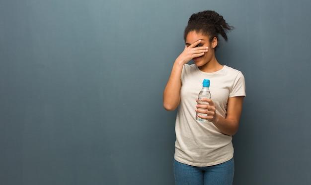 Giovane donna di colore imbarazzata e ridente allo stesso tempo. tiene in mano una bottiglia d'acqua.