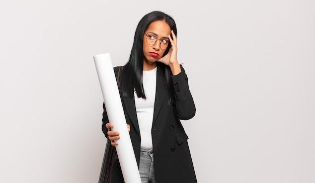 Giovane donna di colore che si sente annoiata, frustrata e assonnata dopo un compito noioso, noioso e noioso, tenendo il viso con la mano. concetto di architetto