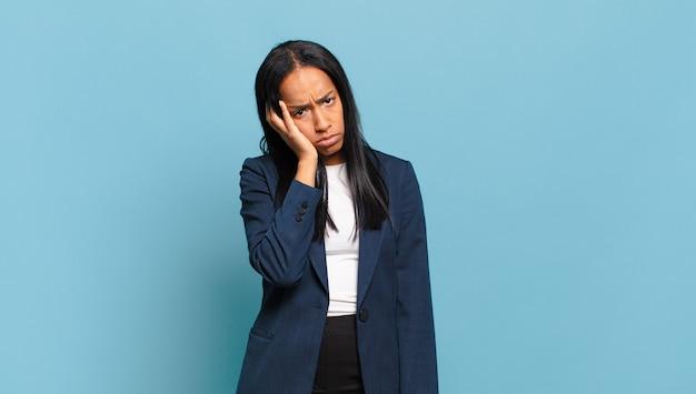 Giovane donna di colore che si sente annoiata, frustrata e assonnata dopo un compito noioso, noioso e noioso, tenendo il viso con la mano. concetto di business