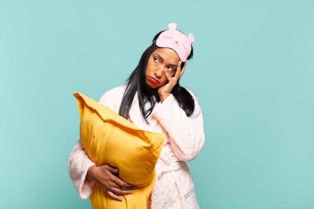 Giovane donna di colore che si sente annoiata, frustrata e assonnata dopo un compito noioso, noioso e noioso, tenendo il viso con la mano. concetto di pigiama