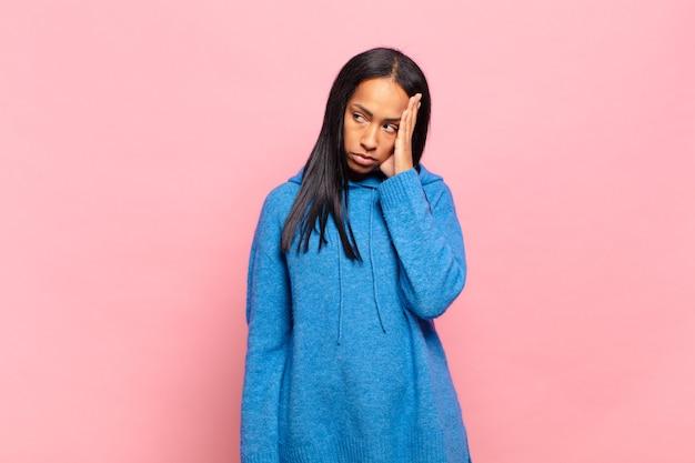 Giovane donna di colore che si sente annoiata, frustrata e assonnata dopo un compito noioso, noioso e noioso, tenendo il viso con la mano