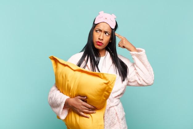 Giovane donna di colore che si sente confusa e perplessa, mostrando che sei pazzo, pazzo o fuori di testa. concetto di pigiama