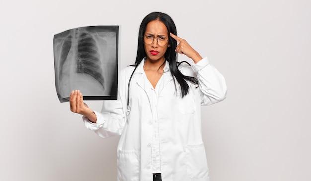 Giovane donna di colore che si sente confusa e perplessa, mostrando che sei pazzo, pazzo o fuori di testa. concetto di medico