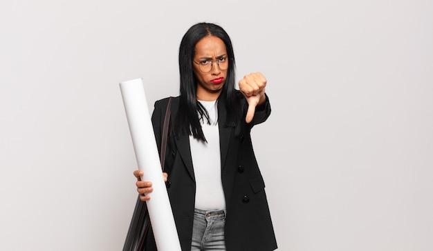 Giovane donna di colore che si sente arrabbiata, arrabbiata, infastidita, delusa o scontenta, mostrando i pollici verso il basso con uno sguardo serio. concetto di architetto