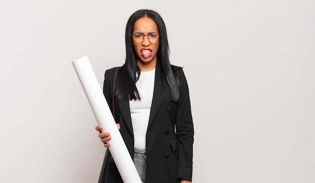 Giovane donna di colore che si sente disgustata e irritata, sporge la lingua, non ama qualcosa di sgradevole e schifoso. concetto di architetto