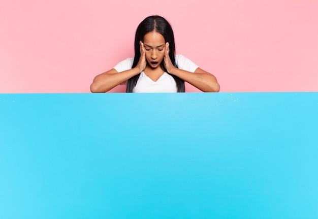 Giovane donna di colore che si sente felice, eccitata e sorpresa, guardando di lato con entrambe le mani sul viso. copia il concetto di spazio