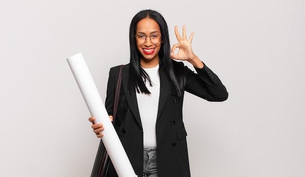 Giovane donna di colore che si sente felice, rilassata e soddisfatta, mostrando approvazione con un gesto ok, sorridente. concetto di architetto