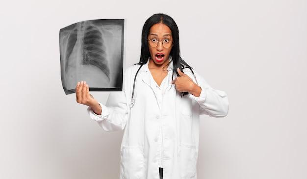 Giovane donna di colore che si sente felice, sorpresa e orgogliosa, indicando se stessa con uno sguardo eccitato e stupito. concetto di medico
