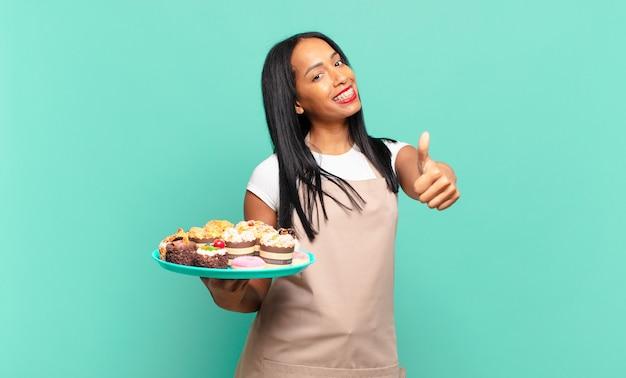 Giovane donna di colore che si sente orgogliosa, spensierata, sicura di sé e felice, sorridendo positivamente con il pollice in alto. concetto di chef di panetteria