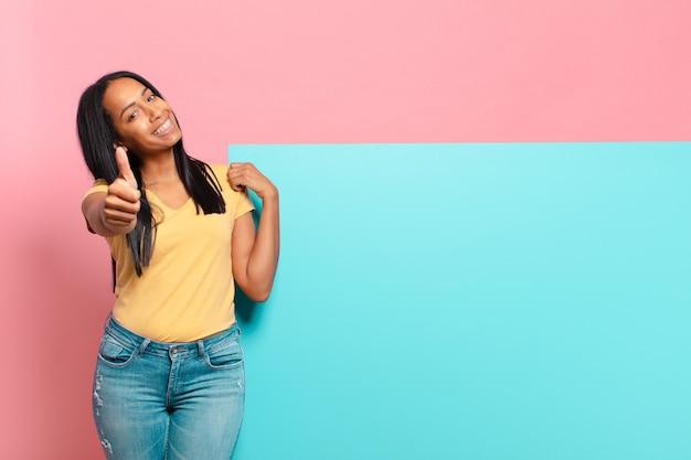 Giovane donna di colore che si sente orgogliosa, spensierata, sicura di sé e felice, sorridendo positivamente con il pollice in alto. copia il concetto di spazio