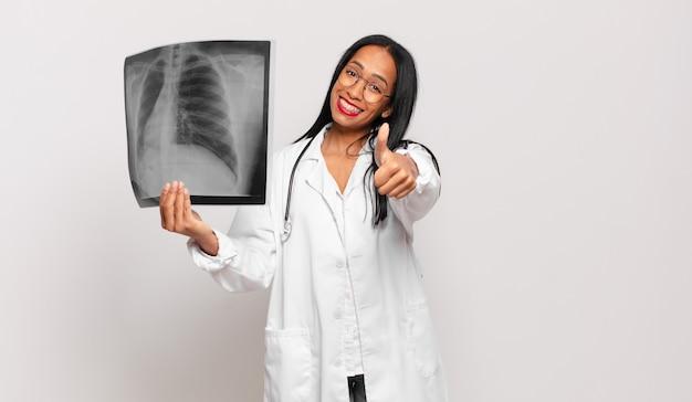 Giovane donna di colore che si sente orgogliosa, spensierata, sicura di sé e felice, sorridendo positivamente con i pollici in su. concetto di medico