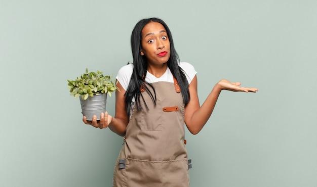 Giovane donna di colore che si sente perplessa e confusa, dubita, appesantisce o sceglie diverse opzioni con un'espressione divertente. concetto di giardiniere