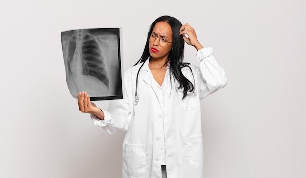 Giovane donna di colore che si sente perplessa e confusa, si gratta la testa e guarda di lato. concetto di medico