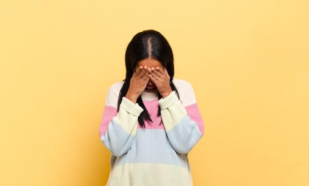 Giovane donna di colore che si sente triste, frustrata, nervosa e depressa, coprendo il viso con entrambe le mani, piangendo