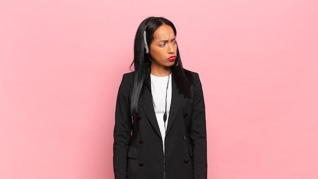 Giovane donna di colore che si sente triste, sconvolta o arrabbiata e guarda di lato con un atteggiamento negativo, aggrottando la fronte in disaccordo. concetto di telemarketing