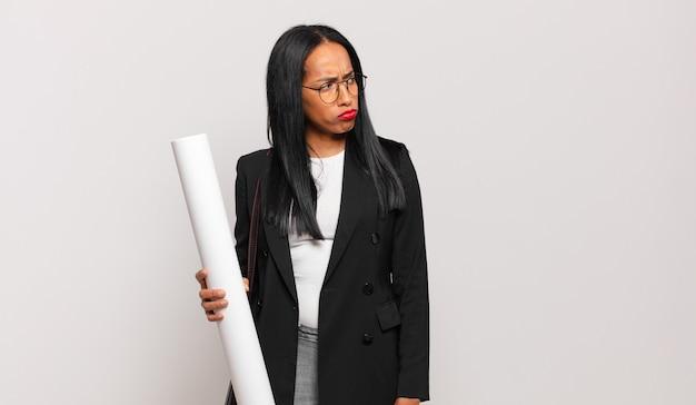 Giovane donna di colore che si sente triste, turbata o arrabbiata e guarda di lato con un atteggiamento negativo