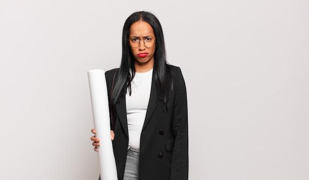 Giovane donna di colore che si sente triste e piagnucolona con uno sguardo infelice, piange con un atteggiamento negativo e frustrato. concetto di architetto