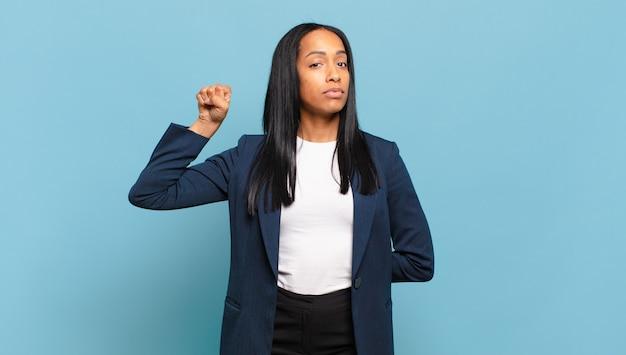 Giovane donna di colore che si sente seria, forte e ribelle, alzando il pugno, protestando o combattendo per la rivoluzione. concetto di business
