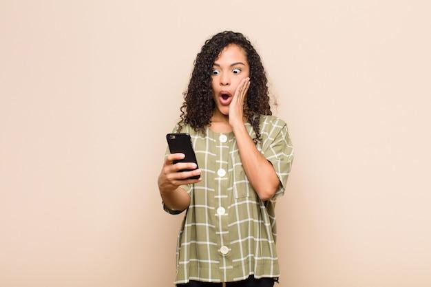 Giovane donna di colore sentirsi scioccata e spaventata, guardando terrorizzata con la bocca aperta e le mani sulle guance con uno smartphone