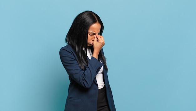 Giovane donna di colore che si sente stressata, infelice e frustrata, tocca la fronte e soffre di emicrania di forte mal di testa. concetto di business