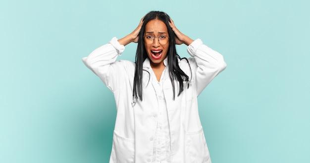 Giovane donna di colore che si sente stressata, preoccupata, ansiosa o spaventata, con le mani sulla testa, in preda al panico per errore. concetto di medico