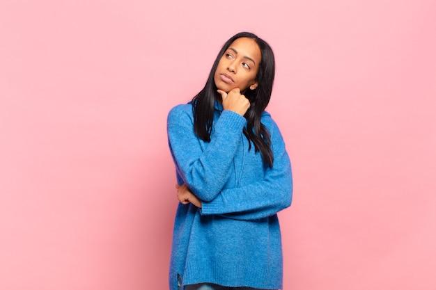 Giovane donna di colore che si sente premurosa, si chiede o immagina idee, sogna ad occhi aperti e alza lo sguardo per copiare lo spazio