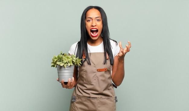 Giovane donna di colore che sembra arrabbiata, infastidita e frustrata che urla wtf o cosa c'è che non va in te. concetto di giardiniere