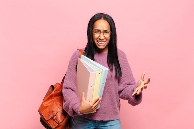 Giovane donna di colore che sembra arrabbiata, infastidita e frustrata che urla wtf